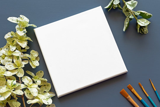 Blank white square canvas on a blue background with green leaves and artist brushes - White empty stretched canvas mockup flat lay