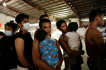 Men carrying their babies queue for food in an evacuation center for residents affected by the Taal Volcano erruption in Santo Tomas