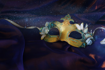 Photo of elegant and delicate gold Venetian mask over purple silk background