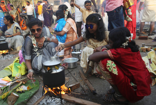 Devotees stand in line to collect utensils and ingredients for preparing ritual rice dishes to offer to the Hindu Sun God as they attend Pongal celebrations at a slum in Mumbai