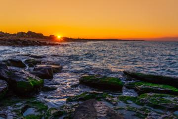 Wave crashing on the rocky seashore at dramatic sunset