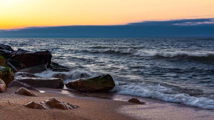 Waves crashing on the rocky seashore at sunset