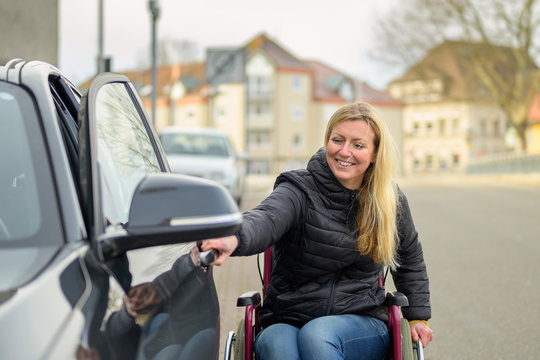 Woman in a wheelchair opening a car door