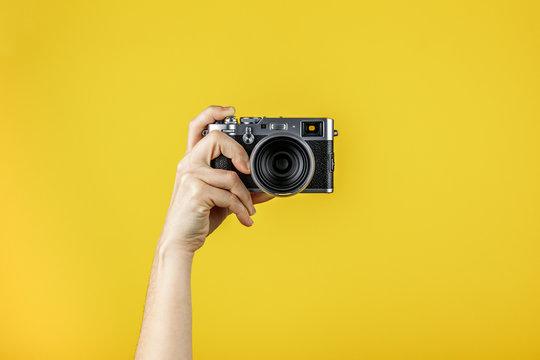 Camera held by one hand in front of a yellow background