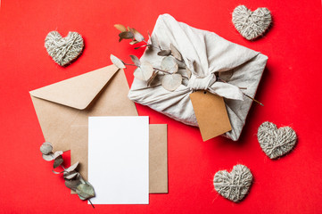 Zero waste Valentine's Day concept and mock up on red. Eco-friendly gift cloth wrapping in Furoshiki style, craft paper envelope,empty greetings card. Top down view or flat lay. Copy space for design
