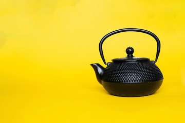 Black cast iron teapot orialtal style on a yellow gold background. Asian culture, the custom of drinking tea concept.