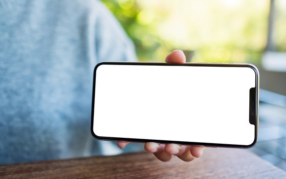 Mockup image of a hand holding and showing black mobile phone with blank desktop screen