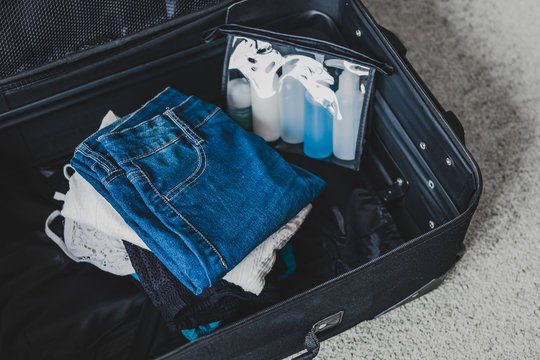 travel essentials and packing light for a holiday concept, luggage with pile of clothes next to transparent liquid bag for airport security screening compliance