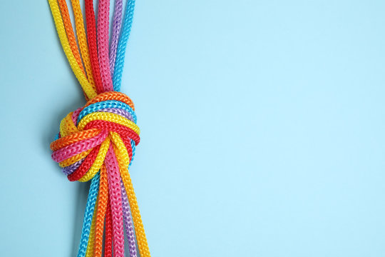 Top view of colorful ropes tied together on light blue background, space for text. Unity concept