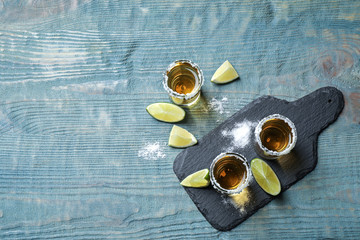 Poster de jardin Bar Mexican Tequila shots, lime slices and salt on blue wooden table, flat lay. Space for text