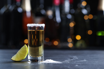 Mexican Tequila shot with lime and salt on bar counter. Space for text
