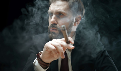 Smoking bearded man wearing dark suit, tie, and watch with hand and cigar forefront isolated over black background