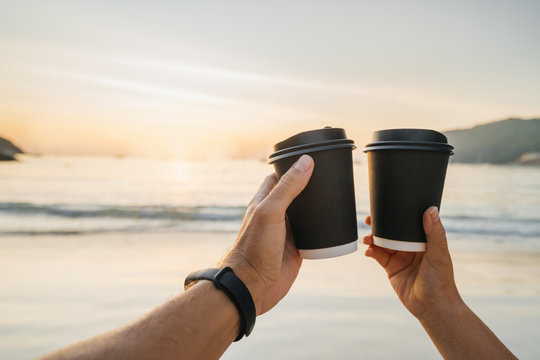 Two disposable paper cups in the hands of a man and a woman against the backdrop of a beautiful sunset and sea landscape. The concept of love, relationship or Valentine's Day celebration.