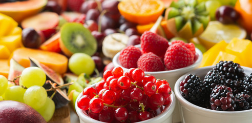 Wall Mural - Long photo, banner, healthy cut fruits background, strawberries raspberries oranges plums apples kiwis grapes red currants blueberries mango persimmon, selective focus