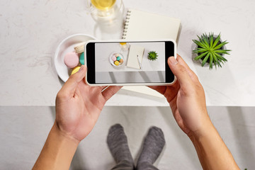 Taking picture of notebook, cake macaron and tea mug on white background. Flatlay