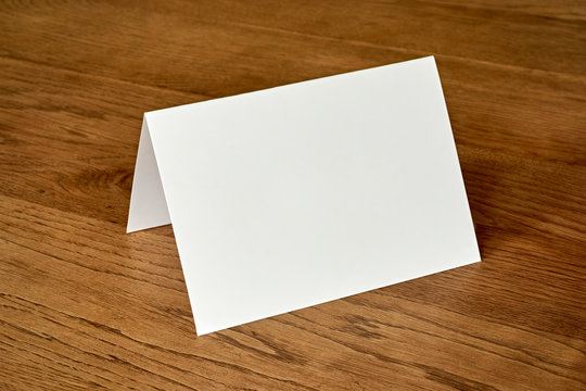 Standing blank empty greeting card mock up on dark wooden background. For use as a Christmas, birthday, wedding or celebration background template.