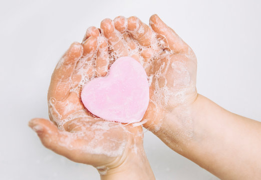 Importance of personal hygiene care. Flat lay view of child washing dirty hands with pink heart shape soap bar, lot of foam. Copy space.