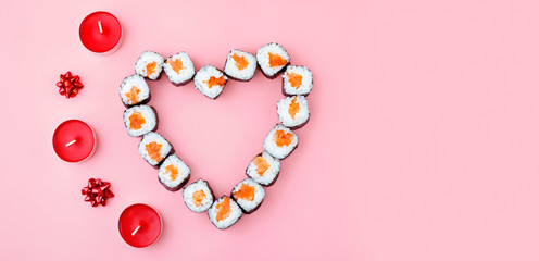 Door stickers Sushi bar Salmon sushi rolls laid out in the shape of a heart, next to red candles and bowson a pink background. The concept of Japanese cuisine for Valentine's Day, greeting card, banner. Copy space