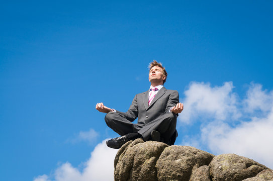 Businessman seated in a yoga pose outdoors balanced on the top of rocky mountain peak