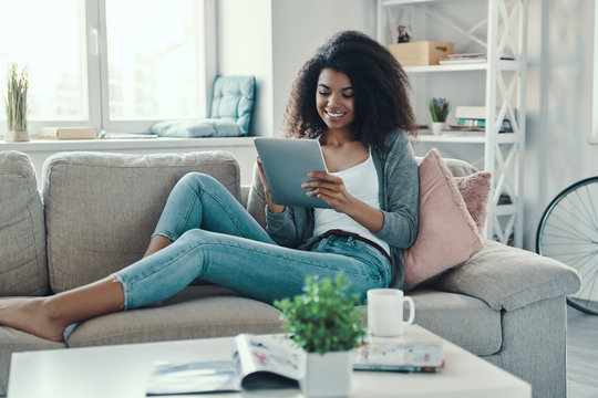 Relaxed young African woman using digital tablet and smiling while resting at home