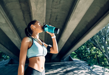 In de dag Ontspanning Young fitness woman drinking water from bottle