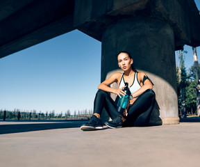 In de dag Ontspanning Young fitness woman relax after work out exercising in industrial city background near river