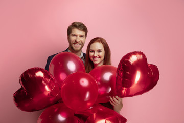 Happy holding balloons shaped hearts. Valentine's day celebration, happy caucasian couple on coral...
