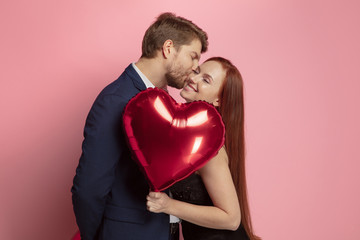 Happy holding balloons shaped hearts. Valentine's day celebration, happy caucasian couple on coral background. Concept of human emotions, facial expression, love, relations, romantic holidays.