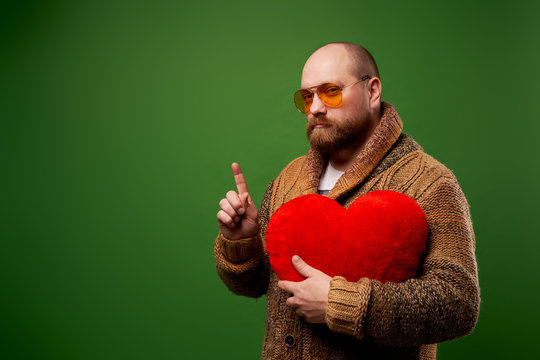 Man in pink glasses holds toy heart while standing on empty green background in studio