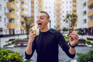 Fotomurales - Attractive sportsman standing outdoors and choosing between candy and fresh banana. In background are buildings.