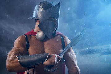 Muscular spartan looking at blade.