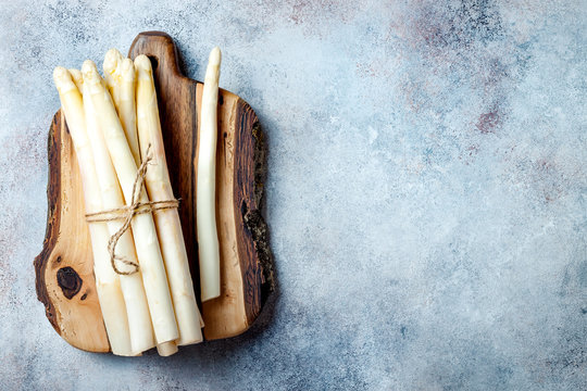 Bunch of raw white asparagus served on wooden board. Top view, copy space