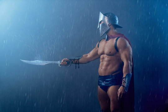 Muscular spartan pointing sword.