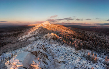 Snow covered mountain range in winter at sunset. Forest and rocks top view