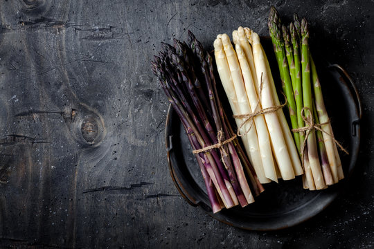 Bunches of fresh green, purple, white asparagus on vintage metal tray over dark grey rustic background. Top view, copy space