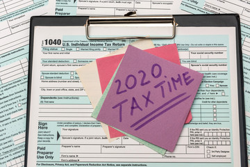 2020 Tax Company. Colorful stickers with reminder at 1040 tax form close up