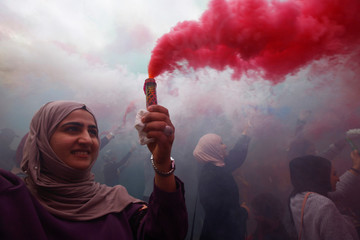 An Iraqi woman waves with a colored smoke candle during the festival of colors, in the holy Shi'ite city of Najaf