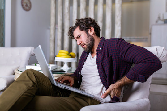 Tired man freelance worker stretch in sofa suffer from sitting long in incorrect posture, male employee have back pain or spinal spasm working in uncomfortable position. Sedentary life concept