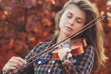 beautiful young woman playing violin on a background of red foliage, romantic girl in dress playing a musical instrument in nature, musical performance outdoors, concept of hobby and passion in art
