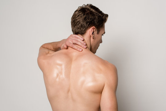 back view of man having neck pain isolated on grey