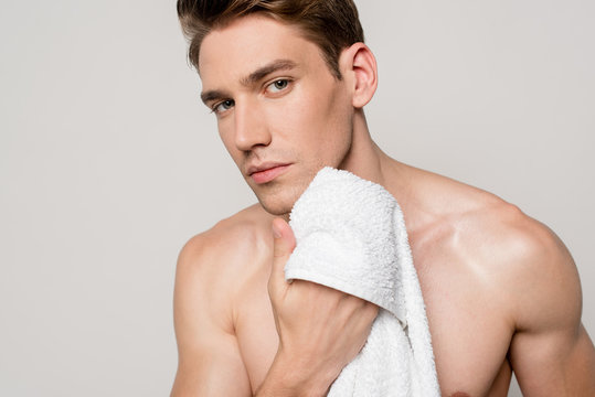 sexy man with muscular torso holding cotton towel isolated on grey