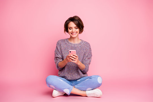 Portrait of her she nice attractive lovely charming pretty cute cheerful cheery brown-haired girl sitting using cell 5g app isolated over pink pastel color background