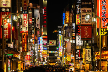 TOKYO, JAPAN - December, 2019: Crowds pass through Kabukicho in the Shinjuku district. The area is an entertainment and red-light district.