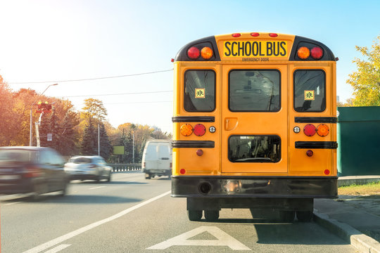 Big classic vintage american yellow schoolbus standing on a bus lane at highway and waiting pupils and children for school trip road. School bus transport back door view on route bright morning time