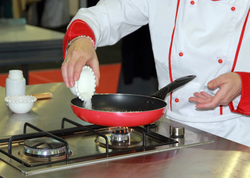 Chef, white sugar poured into a pan to fried.