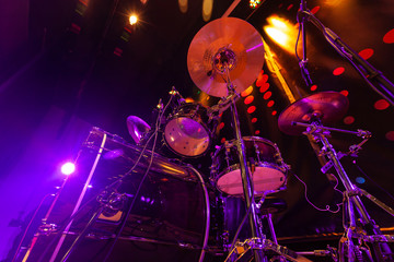 Drum set with bass drum, tom-toms, cymbals and microphones on the stage with violet-red illumination
