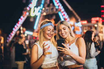 Two girls taking selfie in the amusement park