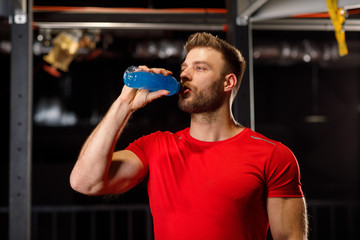 Young handsome man drinking energy drinks at the gym