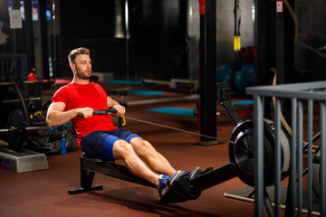 Young Muscular Fit Man using Rowing Machine at Gym