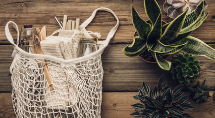 Collection of various succulent plants and Mesh market bag with bamboo cutlery, reusable bottles and eco cotton bags on wooden background